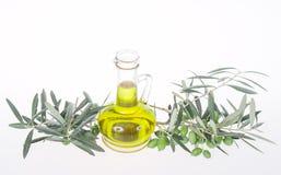 Glasflaska med extra jungfrulig olivolja och olivgröna filialer Olivträdfrunch med oliv som isoleras på vit bakgrund royaltyfria bilder