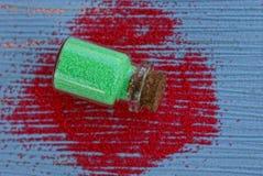 Glasflaskan med grön sand ligger på en blå tabell i röd sand Fotografering för Bildbyråer