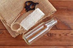 Glasflaskan sax, säckväv, kabel, snör åt Ställ in för handgjord vas Lantlig stil diy begrepp Brun trätabell Arkivfoto