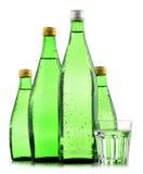 Glasflaskor av mineralvatten som isoleras på vit Arkivfoto
