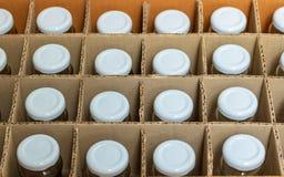 Glasflaskor med vita kapsyler i en kartong, överkant tävlar arkivfoto