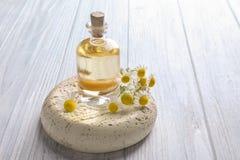 Glasfles met etherische olie en verse kamillebloemen Royalty-vrije Stock Afbeelding