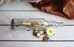 Glasfles met het bericht op een witte houten oppervlakte met overzees Stock Fotografie