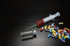 Glasflesje, Spuit en Kleurrijke Pillen op Zwarte Houten Backgro Stock Afbeeldingen