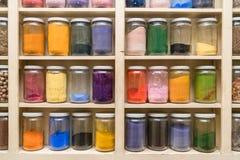 Glasflessen met kleurrijke kruiden op shelfs Stock Foto