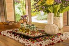 Glasflessen met parfums en bloemen op de houten lijst bij het KUUROORD royalty-vrije stock fotografie