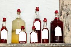 Glasflessen van verschillende grootte met verzegelde likeuren Stock Afbeelding