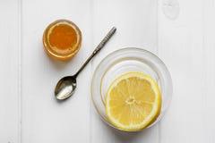 Glasgefäß des Honigs und des silbernen Löffels mit einer Zitrone auf einer Textiltischdecke Stockfotografie