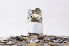Glasgefäß füllte mit Münzen auf einer Gruppe Münzen Lizenzfreies Stockbild