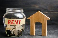 Glasgefäß mit Münzen und das Aufschrift ` mieten ` und ein kleines Holzhaus Miete des Eigentums, Wohnungen Services eines Grundst lizenzfreie stockbilder