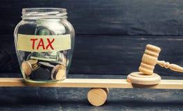Glasgefäß mit Münzen und der Aufschrift 'Steuer 'auf den Skalen Getrennt auf weißem background Gericht und Urteil Gerechtigkeit u stockfoto