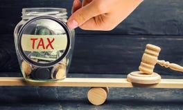 Glasgefäß mit Münzen und der Aufschrift 'Steuer 'auf den Skalen Getrennt auf weißem background Gericht und Urteil Gerechtigkeit u lizenzfreie stockfotos