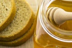 Glasgefäß mit süßem Honig auf hölzernem Stock und Scheiben brot Lizenzfreies Stockfoto