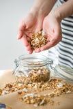 Glasgefäß selbst gemachtes organisches Granola mit Kokosnuss und Pekannüssen auf dem Backpapierhintergrund Köstliche Frühstücksko Lizenzfreie Stockbilder