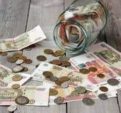 Glasgefäß und russisches Geld auf dem Bretterboden Lizenzfreie Stockbilder