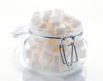 Glasgefäß voll Würfel des raffinierten Zuckers Lizenzfreie Stockbilder