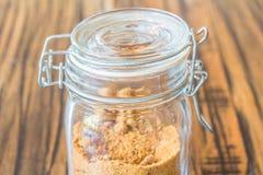 Glasgefäß Zucker auf Holztisch Stockfotos
