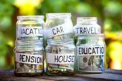 Glasgefäße mit Dollar und Text: Haus, Auto, Reise, Bildung, Pension Lizenzfreie Stockbilder
