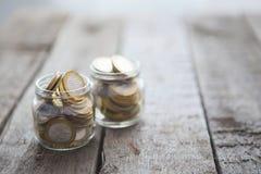Glasgefäße mit Geld prägt Rubel 10-Rubel-Münzen Stockbilder