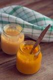 Glasgefäße mit natürlicher Säuglingsnahrung auf dem Holztisch Lizenzfreies Stockfoto