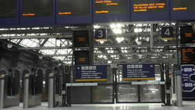 Glasgow Central Railway Station billboard and gates to platforms stock video