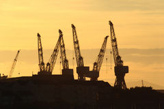 Glasgow cranes. Shipbuilding cranes silhouetted against a Glasgow sunset stock photos