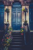 Glasgow Tenement Front Door and Stairs With Spring Flower Pots. Blue Glasgow Tenement Door With Spring Flowers Royalty Free Stock Photos