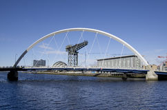Glasgow waterfront with squinty bridge. River Clyde in Glasgow with bridge, crane and modern buildings Royalty Free Stock Photos