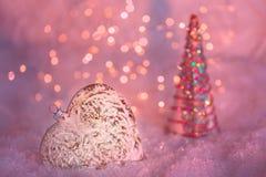 Glasherz auf einem Schnee und getonter unscharfer rosa Hintergrund des funkelnden bokeh mit glühenden Lichtern neue Ideen, das Ha stockfotos