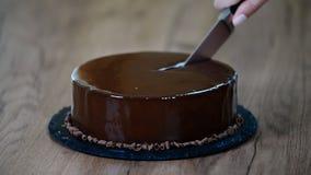 Glasierender Schokoladencremekuchen, Nahaufnahme Schneiden Sie ein Stück des Schokoladenkuchens mit einem Messer stock video footage