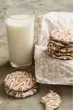 Glasig-glänzende Plätzchen und ein Glas Milch Stockbild