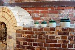 Glasig-glänzende Tonwaren auf einer Backsteinmauer neben einem Brennofen lizenzfreies stockbild