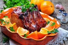 Glasig-glänzender Schweinebratenknochen in der orange Soße mit Paprika und Knoblauch Lizenzfreies Stockfoto