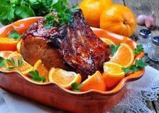 Glasig-glänzender Schweinebratenknochen in der orange Soße mit Paprika und Knoblauch Lizenzfreies Stockbild