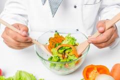 Glaskom met een nuttige plantaardige salade, en kok Stock Foto