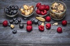 Glaskommen met ingrediënten voor gezond ontbijt - muesli, bessen en noten op blauwe rustieke houten achtergrond Royalty-vrije Stock Foto