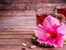 Glaskop met de rode bloem van de thee roze hibiscus op donkere houten achtergrond Royalty-vrije Stock Fotografie