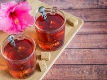 Glaskop met de rode bloem van de thee roze hibiscus op donkere houten achtergrond Royalty-vrije Stock Foto's