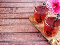 Glaskop met de rode bloem van de thee roze hibiscus op donkere houten achtergrond Royalty-vrije Stock Afbeeldingen