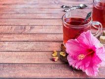 Glaskop met de rode bloem van de thee roze hibiscus op donkere houten achtergrond Stock Fotografie