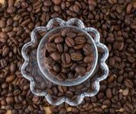 Glaskop op schotel met koffie hierboven bonen op houten lijstmening van Stock Foto's