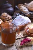 Glaskop thee en broodjes met papaver in een houten kop thee van het mandglas en broodjes met papaver stock afbeelding