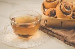 glaskop thee en broodjes met papaver in een houten mand/glaskop thee en broodjes met papaver in een houten mand op een witte lijs royalty-vrije stock foto