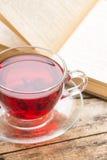 Glaskop van Karkade-thee met oud geopend boek bij de lijst Royalty-vrije Stock Foto