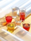 Glaskoppen met kleurrijke koude dranken op een gele achtergrond met extra elementen het schieten met hard licht royalty-vrije stock afbeelding