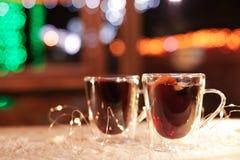 Glaskoppen van overwogen die wijn en slinger op lijst met sneeuw in openlucht wordt behandeld royalty-vrije stock foto
