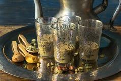 Glaskoppen van Pakistaanse thee met kruiden in een dienblad en een theepot royalty-vrije stock afbeelding