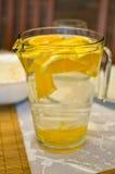 Glaskrug mit Süßwasser und Orangen Stockbild