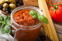 Glaskruik met de eigengemaakte saus van tomatendeegwaren Royalty-vrije Stock Foto