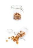 Glaskruik met geïsoleerde die pinda's wordt gevuld Royalty-vrije Stock Foto's
